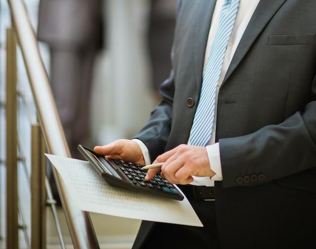 Männerhände mit taschenrechnerberechnung im büro