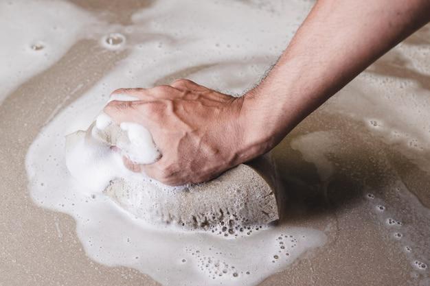 Männerhände reinigen den fliesenboden mit einem schwamm.