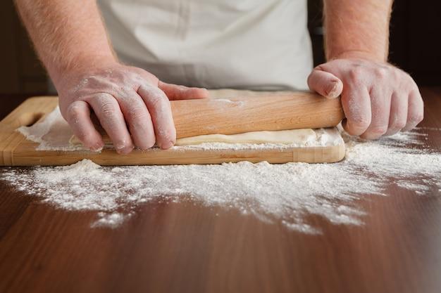 Männerhände rollen teig nah oben aus. mann, der teig für das kochen von nudeln auf einem holztisch vorbereitet