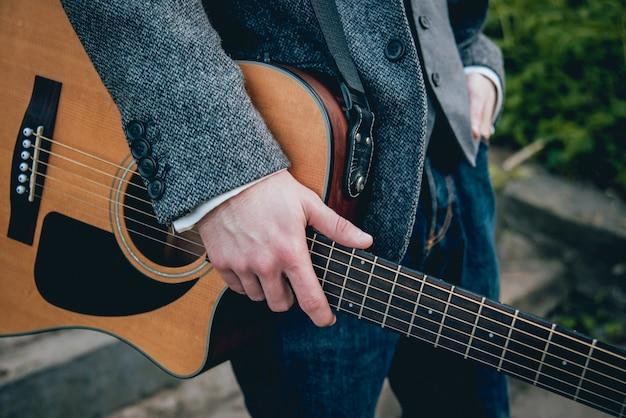 Männerhände spielen akustische gitarre