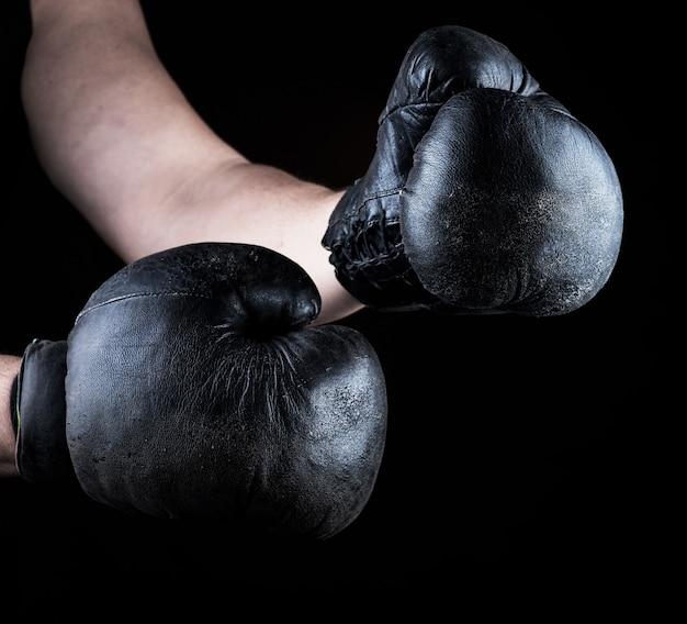 Männerhände tragen alte schwarze boxhandschuhe aus leder