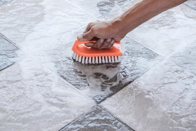 Männerhände werden verwendet, um die polierreinigung auf dem fliesenboden umzuwandeln.