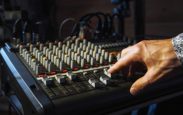 Männerhand auf dem sound mixer