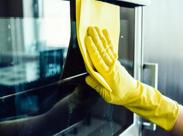 Männerhand, die den küchenofen reinigt