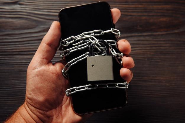 Männerhand, die ein smartphone mit vorhängeschloss hält. konzept des smartphone-schutzes gegen malware, antivirus