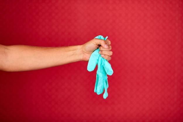 Männerhand, die medizinische blaue latexhandschuhe des schutzes auf rotem studiohintergrund, coronavirus-schutzausrüstung während der covid-19-pandemie hält