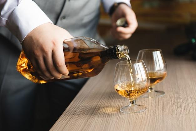 Männerhand gießt whisky in gläser