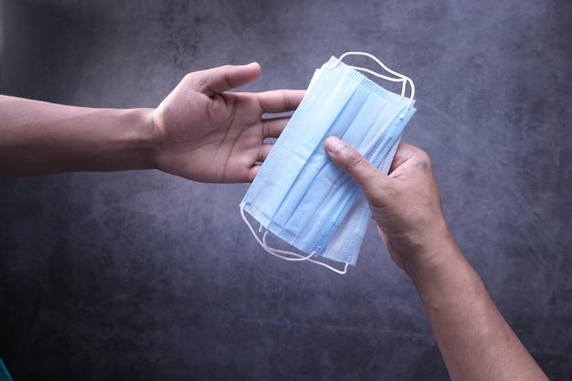 Männerhand hält schutzmaske von oben nach unten