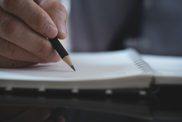 Männerhand mit bleistiftschrift auf notizbuch
