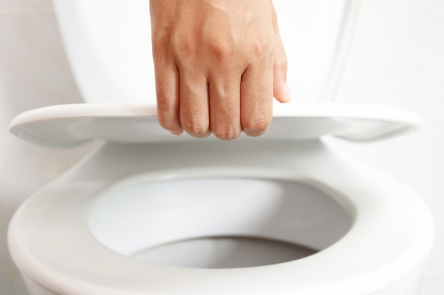 Männerhand öffnet den toilettendeckel
