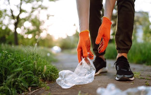 Männerhand sammelt plastikmüll für die reinigung im park. freiwillige, die schutzhandschuhe tragen, sammeln flaschenplastik.