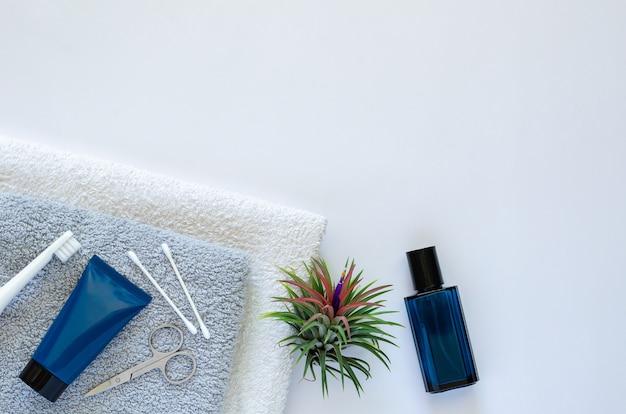 Männerpflegemittel im modernen lebensstil auf handtüchern mit luftpflanze tillandsia auf weißem hintergrund.