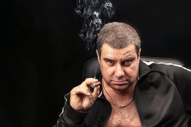 Männerporträt, ein mann, der eine zigarre raucht. erfahrener verbrecher rauchen einer zigarre auf einem stuhl sitzend.