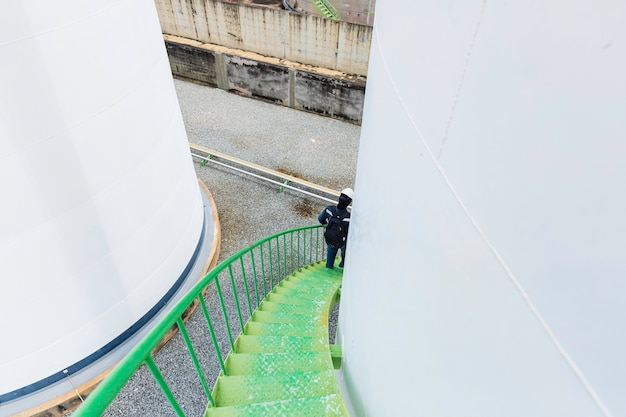 Männlich, der die treppe hinunter in die visuelle aufzeichnung des lagertanks auf der seite geht.
