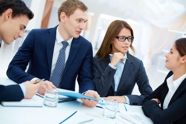 Männlich executive einen blauen ordner in der sitzung halten