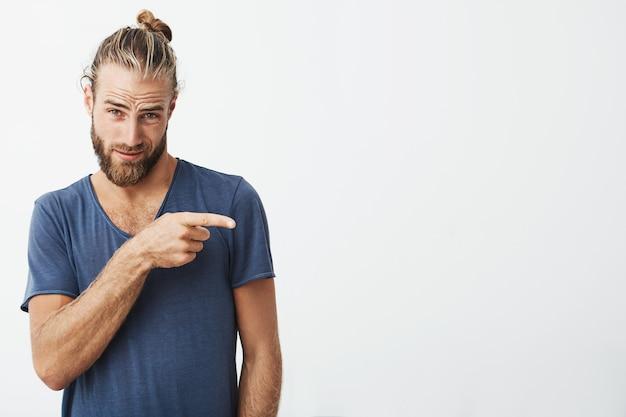 Männlich schöner kerl mit trendiger frisur und bart mit flirtendem gesichtsausdruck, der beiseite zeigt