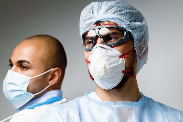 Männliche ärzte in schützender medizinischer uniform im krankenhausporträt