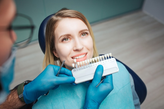 Männliche ärzte stehen auf dem klienten und setzen künstliche zähne auf echte. bleaching-verfahren oder zahnersatz. kundin sitzt auf stuhl und schaut auf. sie zeigt ihre weißen zähne.