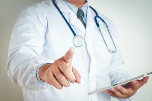 Männliche ärzte tragen eine krawatte, halten eine tablette, sehen die behandlungsinformationen, heben die rechte hand und den zeigefinger.