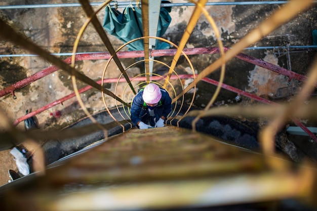 Männliche ansicht von oben klettern die treppe leiter lagerung visuelle inspektion tanköl