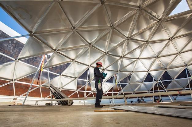 Männliche arbeiter akte aufzeichnung sichtprüfung tank in den beengten raum ist die beleuchtung dachkuppel aluminium beengten raum.