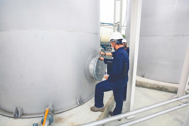 Männliche arbeiter arbeiten für die industrie visuelle inspektion von edelstahltanks für tankstellen.