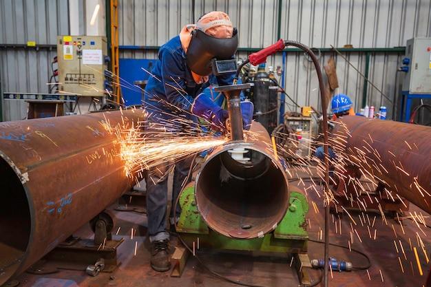 Männliche arbeiter beim schleifen verwenden elektrische schleifrohrfunken im industriebau.