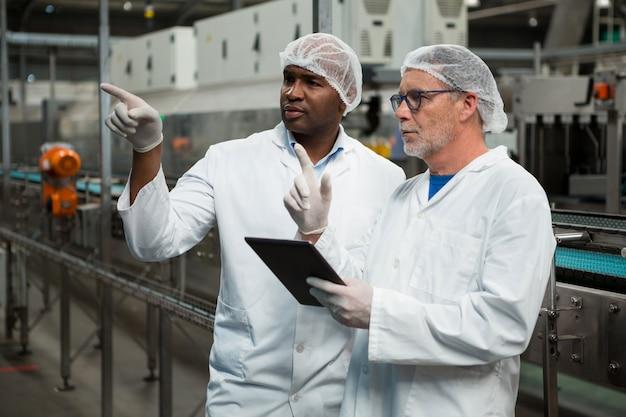 Männliche arbeiter, die in der fabrik für kalte getränke arbeiten