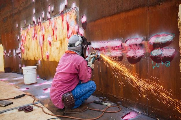 Männliche arbeiter, die mit funkenschlag auf stahlplatte schleifen, tragen schutzhandschuhe öl in engen räumen.
