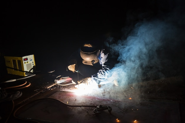 Männliche arbeiter, die schutzkleidung tragen, reparieren bodenplatte lagertank öl industriebau rauch in engen räumen.