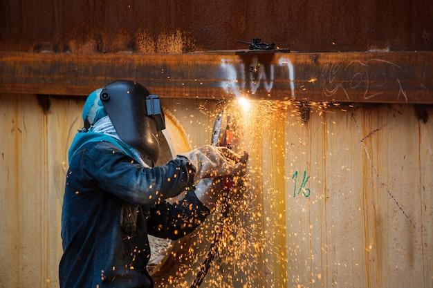 Männliche arbeiter, die schutzkleidung tragen und das schweißen von funkenschalenplatten für industriebauöl und -gas oder lagertanks in engen räumen reparieren.