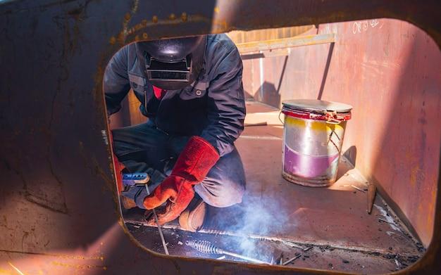 Männliche arbeiter, die schutzkleidung tragen und ponton-schachtschweißen von rauch für industriebauöl-schwimmerlagertank in engen räumen reparieren.