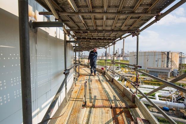 Männliche arbeiter, die sicherheitsgurte und sicherheitsleinen tragen, die an einem hohen gerüst arbeiten.