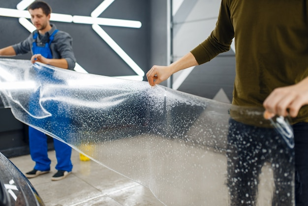 Männliche arbeiter halten eine vorlage aus transparentem autoschutzfilm. anbringen einer beschichtung, die den lack des autos vor kratzern schützt. neufahrzeug in garage, tuning-vorgang Premium Fotos