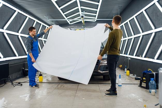 Männliche arbeiter halten haubenschablone aus autoschutzfolie. anbringen einer beschichtung, die den lack des autos vor kratzern schützt. neufahrzeug in garage, tuning-vorgang