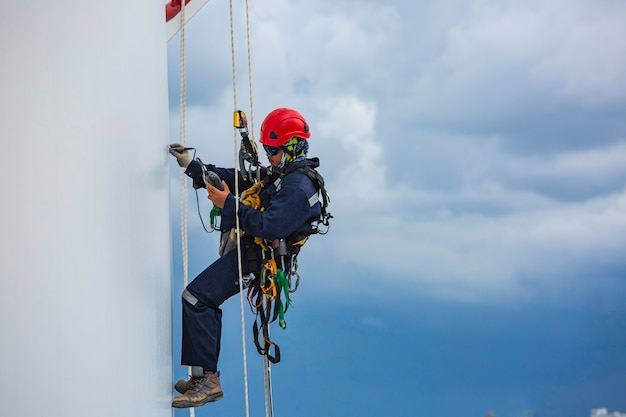 Männliche arbeiter in der nähe steuern ausrüstung abseilen tank seilzugangsinspektion der dicke shell platte lagertank gas hintergrund wolkensturm.