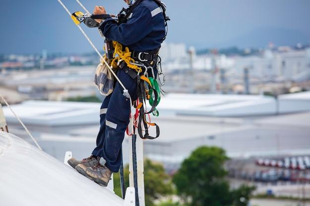 Männliche arbeiter in der nähe steuern ausrüstungsseil nach unten auf dem dach des tanks seilzugangsinspektion der dicke der mantelplatte des lagertanks gassicherheitsarbeiten in der höhe.