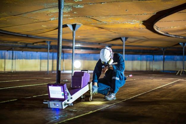 Männliche arbeiter inspektion reinigung boden scan tank externes schwimmen der rostwand verlieren die dicke der bodenplatte nach begrenzten spezifikationen