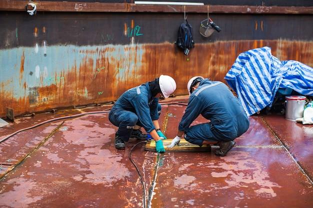 Männliche arbeiter inspektion vakuumtest bodenplatte tank petrochemischer stahl schweißleckage