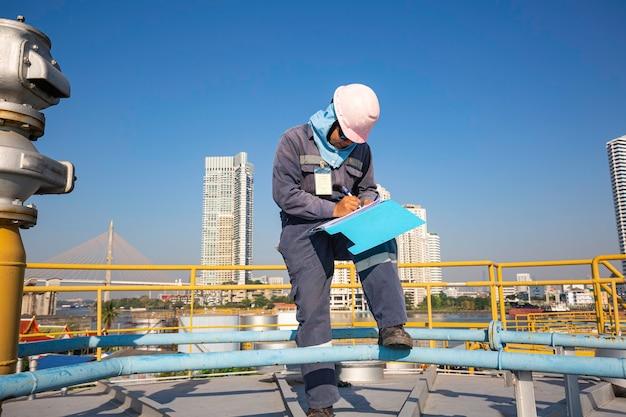 Männliche arbeiter inspektion visuelle dachlagertank öl hintergrund stadt und blauer himmel