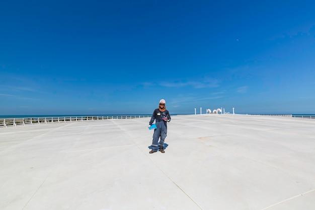Männliche arbeiter inspektion visuelle dachlagertank ölstadt und blauer himmel