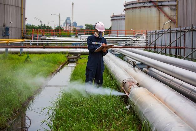Männliche arbeiter inspektion visuelle pipeline öl- und gaskorrosion rosten durch muffenrohr-dampfgas-leckleitung an der isolierung.