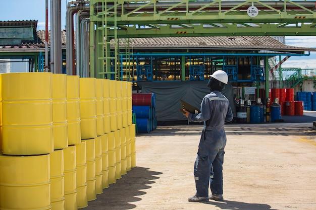 Männliche arbeiter inspektionsaufzeichnung fassölvorrat fässer gelb vertikal oder chemisch für die industrie.