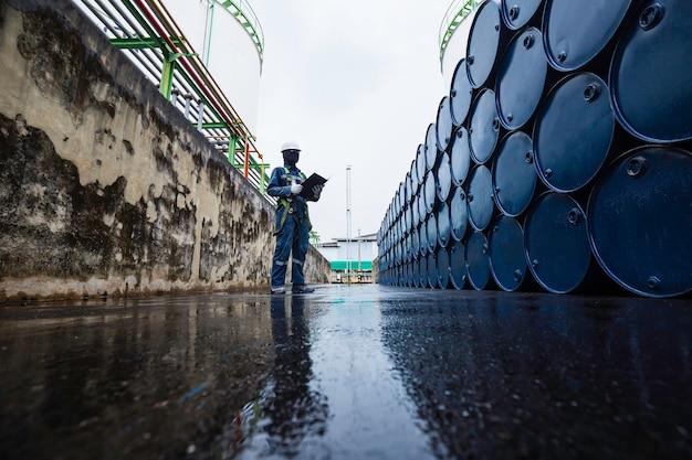 Männliche arbeiter inspektionsaufzeichnung trommelöl lagerfässer blau horizontal oder chemisch für die industrie.