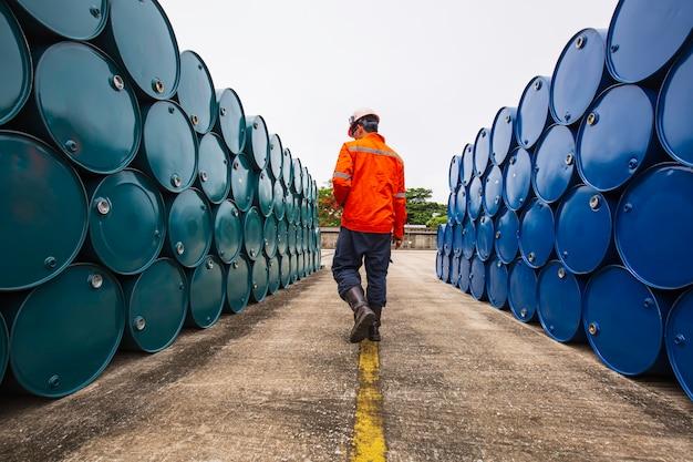 Männliche arbeiter inspektionsaufzeichnung trommelöl lagerfässer blau und grün horizontal oder chemisch für die industrie.