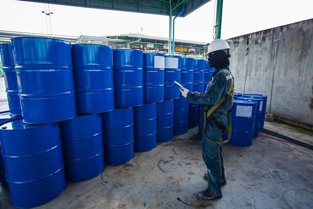 Männliche arbeiter inspektionsaufzeichnung trommelöl lagerfässer blau vertikal oder chemisch für die industrie.