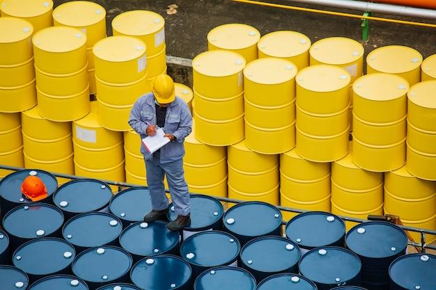 Männliche arbeiter inspektionsaufzeichnung trommelöl lagerfässer gelb vertikal oder chemisch für transportwagen männlich in der industrie.