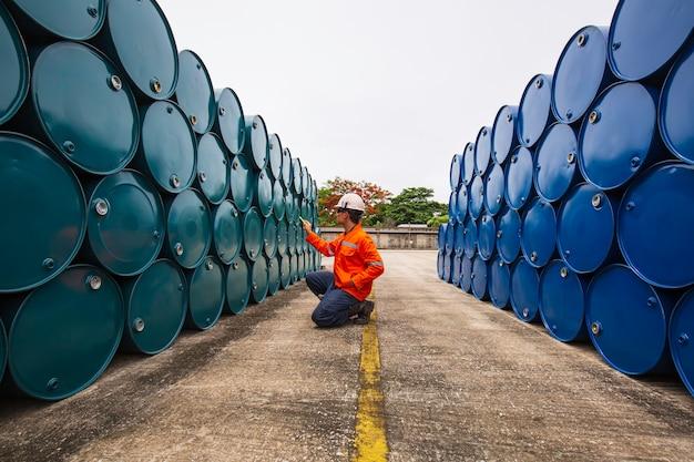 Männliche arbeiter inspektionsaufzeichnung trommelölvorrat fässer blau und grün horizontal oder chemisch für die industrie.