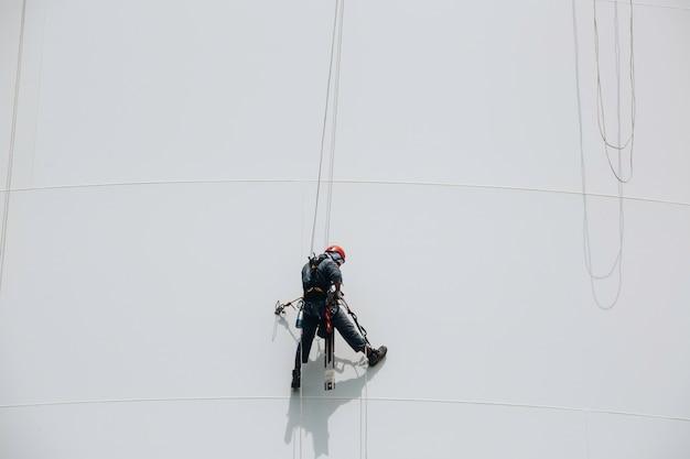 Männliche arbeiter kontrollieren die inspektion des zugangs zum tankseil in der höhe des schwenkseils der dicke der rohrleitung und des tankgases