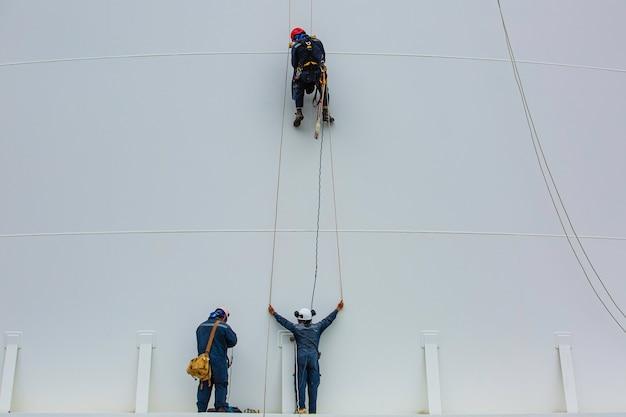 Männliche arbeiter kontrollieren die seilzugangsinspektion des tanks in der höhe von der dicke der panzerplatten-lagertanksicherheitsarbeit in der höhe.